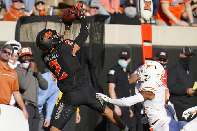 Oklahoma State wide receiver Tylan Wallace (2) jumps to catch a pass in front of Texas defensive back Josh Thompson (9) during the first half of an NCAA college football game in Stillwater, Okla., Saturday, Oct. 31, 2020. (AP Photo/Sue Ogrocki)