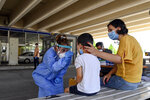 A health worker wearing protective gear takes swab samples from tourists to test for the coronavirus, at Promahonas border crossing with Bulgaria, which is the only land border into Greece that is open on Monday, July 6, 2020. Dozens of vehicles of Serb holidaymakers who were trapped at the Greek border overnight have been allowed to cross into Greece after a ban on the entry of people from Serbia came into effect due to a coronavirus flare-up in Serbia. (AP Photo/Giannis Papanikos)