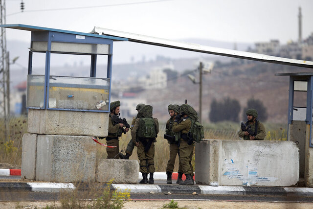 Israeli soldiers secure the area after a Palestinian gunman opened fire at a military post and troops returned fire, at the Huwara checkpoint south of the West Bank city of Nablus, Wednesday, Nov. 4, 2020. The military said the gunman was killed and no troops were wounded. (AP Photo/Majdi Mohammed)