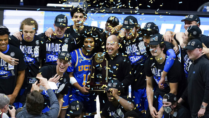UCLA players and coaches celebrate after an Elite 8 game against Michigan in the NCAA men's college basketball tournament at Lucas Oil Stadium, Wednesday, March 31, 2021, in Indianapolis. UCLA won 51-49. (AP Photo/Darron Cummings)