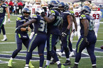 Seattle Seahawks quarterback Russell Wilson, left, greets running back DeeJay Dallas (31), second from left, after Dallas scored a touchdown against the San Francisco 49ers during the second half of an NFL football game, Sunday, Nov. 1, 2020, in Seattle. The Seahawks won 37-27. (AP Photo/Elaine Thompson)