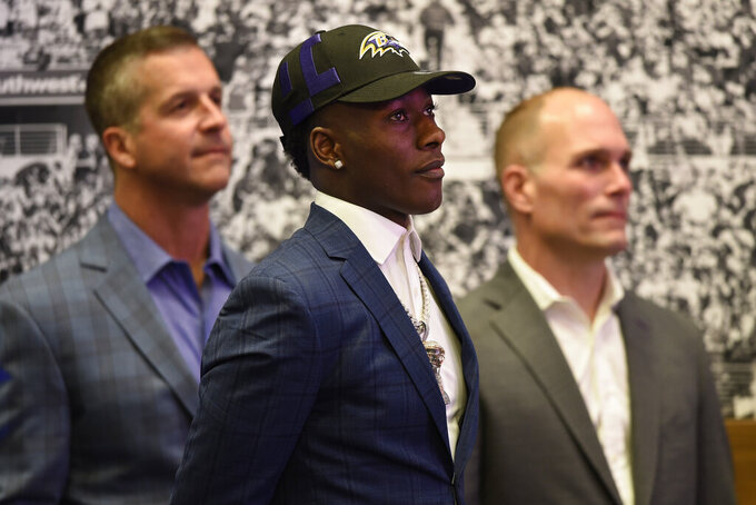 Baltimore Ravens NFL football first round draft pick Marquise Brown, center, stands with head coach John Harbaugh, left, and Executive Vice President/General Manager Eric DeCosta before being introduced to the media Friday, April 26, 2019, in Owings Mills, Md. (AP Photo/Gail Burton)