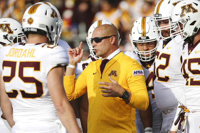 FILE - In this Thursday, Aug. 30, 2018 file photo, Minnesota head coach P.J. Fleck talks with his team prior to an NCAA college football game against New Mexico State in Minneapolis. Minnesota coach P.J. Fleck watched big play after big play by Illinois last weekend and knew a change was needed. The Illini's first two drives each culminated with a 72-yard touchdown run by Reggie Corbin. Fleck fired defensive coordinator Robb Smith on Sunday, Nov. 4, 2018.(AP Photo/Stacy Bengs, File)