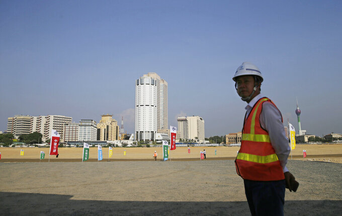 FILE - In this Jan. 2, 2018, file photo, a Chinese construction worker stands on land that was reclaimed from the Indian Ocean for the Colombo Port City project, initiated as part of China's ambitious One Belt One Road initiative, in Colombo, Sri Lanka. Sri Lanka's top court , Tuesday, May 18, 2021, has ordered that some provisions of a legislation to set up a powerful economic commission in a Chinese-built port city violate the constitution and require approval by a public referendum to become law. (AP Photo/Eranga Jayawardena, File)