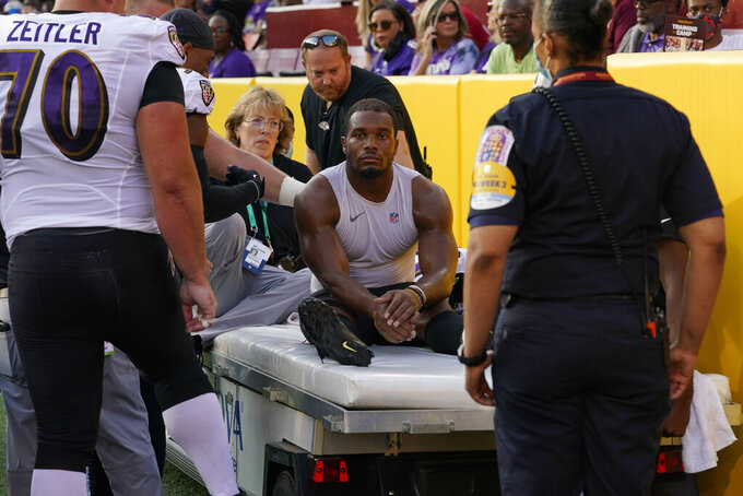 Baltimore Ravens running back J.K. Dobbins (27) is taken off the field after suffering an injury in the first half of a preseason NFL football game against the Washington Football Team, Saturday, Aug. 28, 2021, in Landover, Md. (AP Photo/Carolyn Kaster)