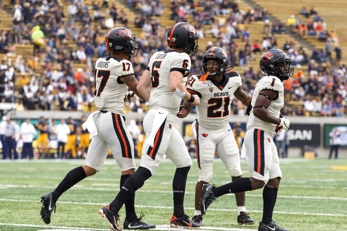 Oregon State running back Artavis Pierce (21) celebrates with quarterback Jake Luton (6), wide receiver Isaiah Hodgins (17) and wide receiver Tyjon Lindsey (1) after scoring a touchdown against the California in the first quarter of an NCAA college football game in Berkeley, Calif., Saturday, Oct. 19, 2019. (AP Photo/John Hefti)