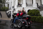 President Donald Trump watches riders from the Truman Balcony of the White House, during a