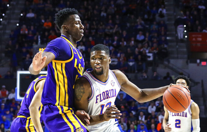 Florida center Kevarrius Hayes (13) is defended by LSU forward Kavell Bigby-Williams, left, during the first half of an NCAA college basketball game in Gainesville, Fla., Wednesday, March 6, 2019. (AP Photo/Gary McCullough)