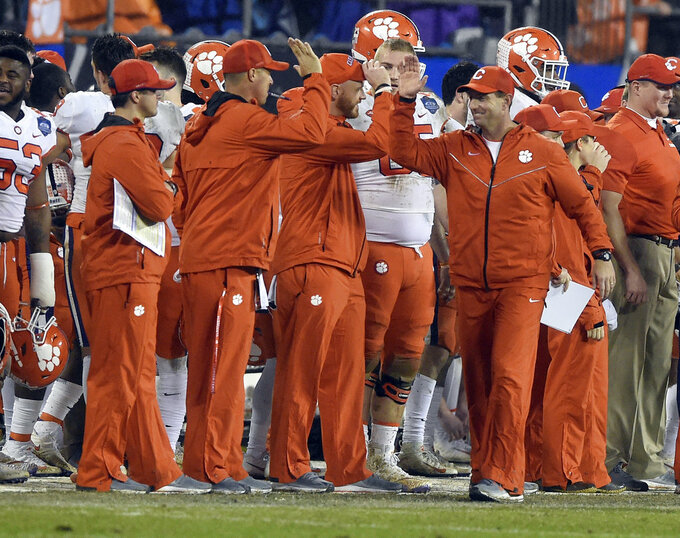 Clemson head coach Dabo Swinney, right, congratulates his coaching staff in the closing seconds of the second half of the Atlantic Coast Conference championship NCAA college football game against Pittsburgh in Charlotte, N.C., Saturday, Dec. 1, 2018. (AP Photo/Mike McCarn)