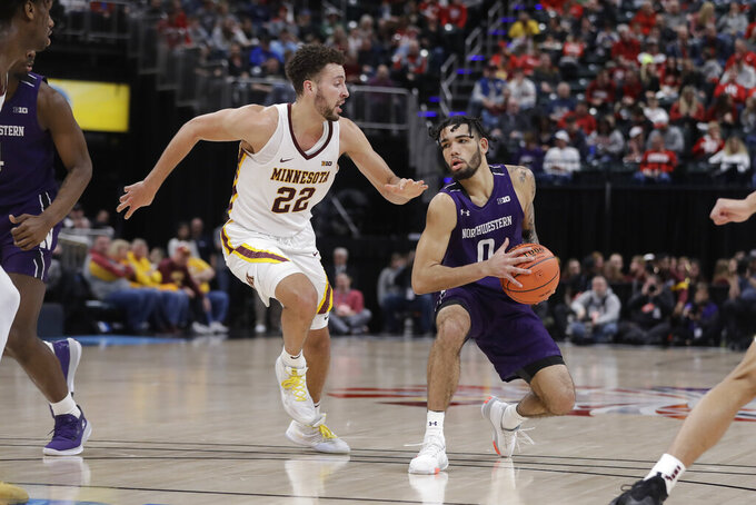 Northwestern's Boo Buie (0) is defended by Minnesota's Gabe Kalscheur (22) during the second half of an NCAA college basketball game at the Big Ten Conference tournament, Wednesday, March 11, 2020, in Indianapolis. Minnesota won 74-57. (AP Photo/Darron Cummings)