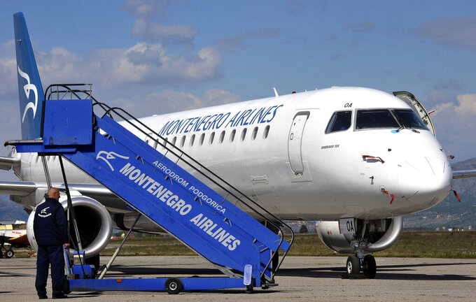 """In this photo taken on April 10, 2014, Montenegro Airlines Embraer E195LR on the tarmac at the Golubovci airport, near Podgorica, Montenegro. Montenegro Airlines ceased its operations on Saturday, Dec. 26, 2020 after the small country's new government refused to continue financing the national carrier. The airline which was formed 25 years ago has apologized to its passengers for the sudden termination of all flights and thanked them for """"the years of trust, travel and friendship."""" (AP Photo/Risto Bozovic)"""