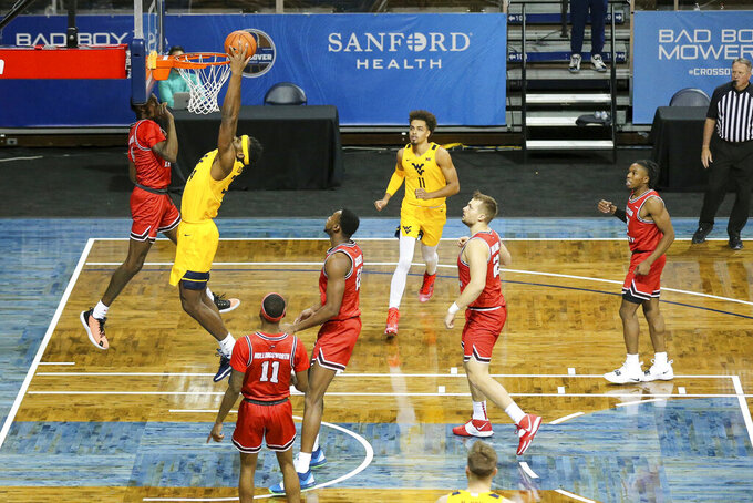 West Virginia forward Oscar Tshiebwe (34) dunks over a Western Kentucky defender during the first half of an NCAA college basketball game Friday, Nov. 27, 2020, in SIoux Falls, S.D. (AP Photo/Josh Jurgens)