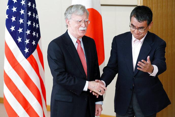 Japanese Foreign Minister Taro Kono, right, escorts U.S. National Security Advisor John Bolton, prior to their meeting in Tokyo Monday, July 22, 2019. (AP Photo/Eugene Hoshiko)