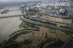 A part of a main road and a park near the Han River are flooded due to heavy rain in Seoul, South Korea, Thursday, Aug. 6, 2020. Torrential rains continuously pounded South Korea on Thursday, prompting authorities to close parts of highways and issue a rare flood alert near a key river bridge in Seoul. (AP Photo/Lee Jin-man)