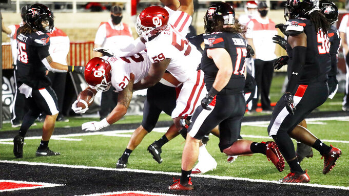 Oklahoma's Jeremiah Hall (27) scores a touchdown in the first half of an NCAA college football game against Texas Tech, Saturday, Oct. 31, 2020, in Lubbock, Texas. (AP Photo/Mark Rogers)