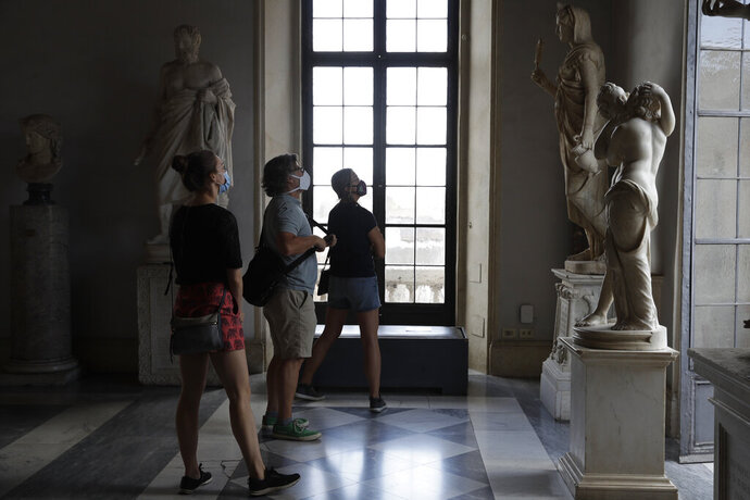 Visitors wearing a face masks to prevent the spread of COVID-19 admire statues in the Rome Capitoline Museums, including the second century A.D. Roman marble statue