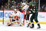 Minnesota Wild left wing Jordan Greenway (18) defects a shot on goal scoring a goal on Calgary Flames goalie David Rittich (33) which defense help from Calgary Flames center Mark Jankowski (77) in the third period during an NHL hockey game Sunday, Jan. 5, 2020, in St. Paul, Minn. The Flames defeated the Wild 5-4 in the shoot out. (AP Photo/Andy Clayton-King)