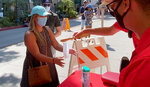 An 'ambassador,' right, hands out masks at outdoor dining areas that have largely taken over State Street in downtown Santa Barbara, Calif., Wednesday, July 29, 2020. After weeks of stressing education over enforcement, California communities say they are now issuing fines and relying on anonymous tips to make sure businesses and residents are complying with health orders requiring masks, disinfection, and social distancing as the state tries to contain the coronavirus. (John Palminteri/KEYT-TV via AP
