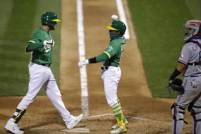 Oakland Athletics' Austin Allen, left, celebrates with Tony Kemp after hitting a two run home run off Texas Rangers' Ian Gibaut in the seventh inning of a baseball game Wednesday, Aug. 5, 2020, in Oakland, Calif. (AP Photo/Ben Margot)