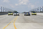 The 2022 Corvette Stingray IMSA GTLM Championship Edition vehicles, left and right, along with a Corvette pace car, center left, and a Corvette C8.R race car, center right, are driven across the MacArthur Bridge toward the Raceway at Belle Isle for a news conference Wednesday, June 9, 2021 in Detroit. (AP Photo/Jose Juarez)