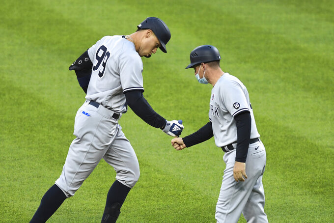 New York Yankees' Aaron Judge is greeted by third base coach Carlos Mendoza after hitting a two-run home run off Baltimore Orioles starting pitcher Jorge Lopez during the second inning of a baseball game Saturday, May 15, 2021, in Baltimore. (AP Photo/Terrance Williams)