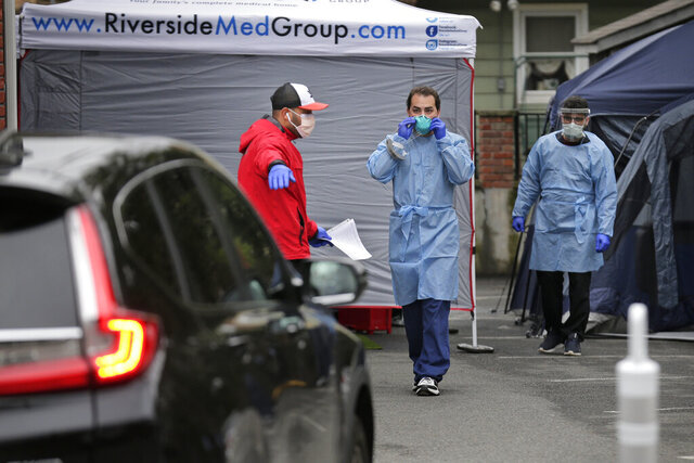 A valet, left, directs a car while medical professionals work at a drive-up testing site for COVID-19 at Riverside Medical Group in Secaucus, N.J., Thursday, March 19, 2020. The testing is only for current patients of Riverside Medical Group. Gov. Phil Murphy said drive-thru testing for coronavirus would begin in Bergen County, the state's hardest-hit area, by Friday and testing in Holmdel, Monmouth County, is expected to begin next week. (AP Photo/Seth Wenig)