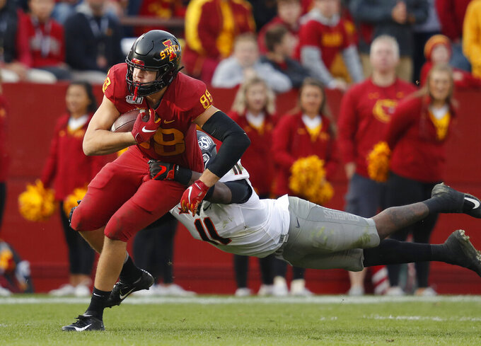Iowa State tight end Charlie Kolar, left, runs the ball as Oklahoma State linebacker Amen Ogbongbemiga, right, leaps to make the tackle during the second half of an NCAA college football game, Saturday, Oct. 26, 2019, in Ames, Iowa. Oklahoma State won 34-27. (AP Photo/Matthew Putney)