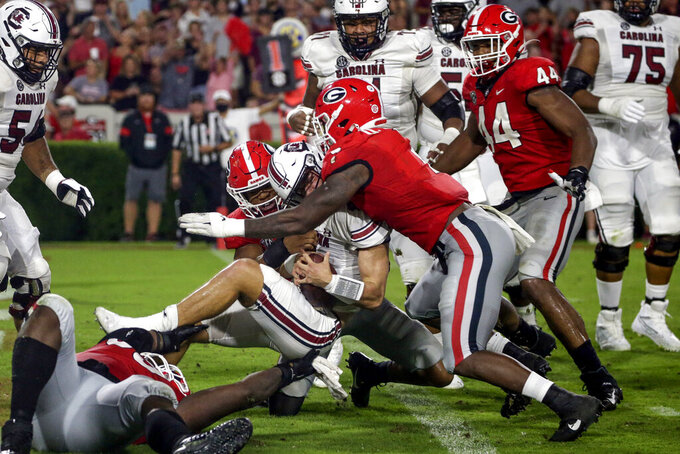 South Carolina quarterback Luke Doty (4) is tacked by linebacker Nolan Smith (4) and Georgia linebacker Quay Walker (7) in the end zone for a safety during the first half of an NCAA college football game Saturday, Sept. 18, 2021, in Athens, Ga. (AP Photo/Butch Dill)