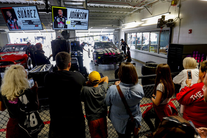 Fans watch the crew for Jimmie Johnson in the new garage facilities during practice for the NASCAR Cup Series auto race at Talladega Superspeedway, Saturday, Oct 12, 2019, in Talladega, Ala. (AP Photo/Butch Dill)