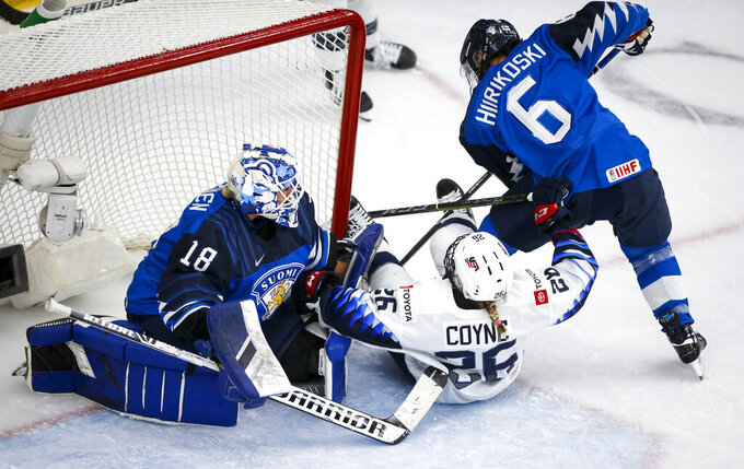 Kendall Coyne Schofield, center, of the United States, is knocked to the ice by Finland's Jenni Hiirikoski, right, as goalie Meeri Raisanen looks on during second period IIHF women's world championship hockey action in Calgary, Alberta, Sunday, Aug. 22, 2021. (Jeff McIntosh/The Canadian Press via AP)