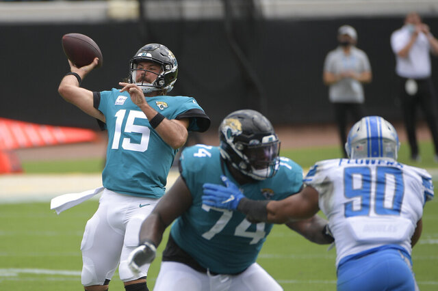 Jacksonville Jaguars quarterback Gardner Minshew II (15) throws a pass as offensive tackle Cam Robinson (74) blocks Detroit Lions defensive end Trey Flowers (90) during the first half of an NFL football game, Sunday, Oct. 18, 2020, in Jacksonville, Fla. (AP Photo/Phelan M. Ebenhack)