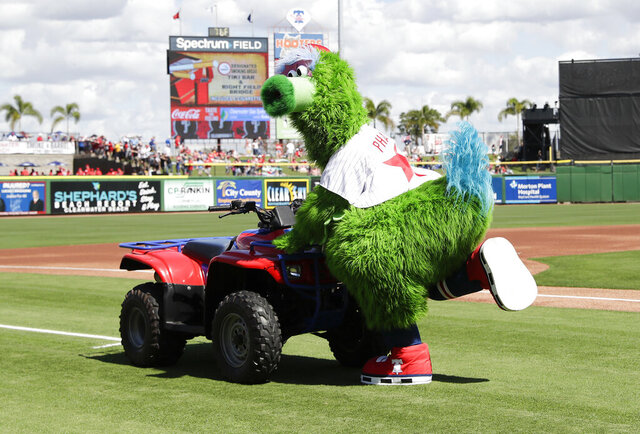 The revamped Phillie Phanatic mascot performs before the Philadelphia Phillies play the Pittsburgh Pirates in a spring training baseball game at Spectrum Field in Clearwater, Fla., Sunday, Feb. 23, 2020. The Phanatic has a new look amid a legal fight with the long-running mascot's creators, but officials say you should not expect his famous attitude to go anywhere. (Yong Kim/The Philadelphia Inquirer via AP)