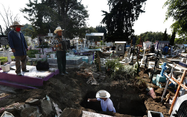 Cemetery musician Victor Dzib Cima, 70, plays his accordion as he waits for clients while cemetery workers remove coffins from gravesites that belonged to families who stopped paying rent at the San Nicolas Tolentino Pantheon, where he has worked for tips for 22 years, in the Iztapalapa area of Mexico City, Friday, May 22, 2020. The cemetery is making space for more burials amid the COVID-19 pandemic, and it is custom for cemeteries in Mexico to rent, instead of sell, grave sites. (AP Photo/Marco Ugarte)