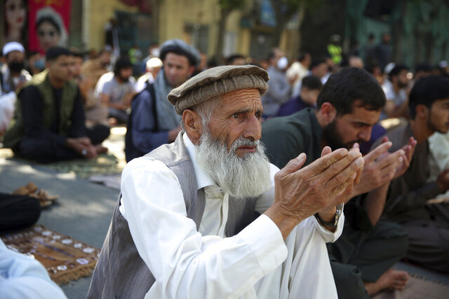 Men pray after the Eid al-Fitr prayers outside a mosque in Kabul, Afghanistan, Sunday, May 24, 2020. The Taliban and Afghanistan's president announced late Saturday a three-day cease-fire ahead of a major Islamic holiday that begins Sunday to mark the end of the Islamic fasting month of Ramadan. (AP Photo/Rahmat Gul)