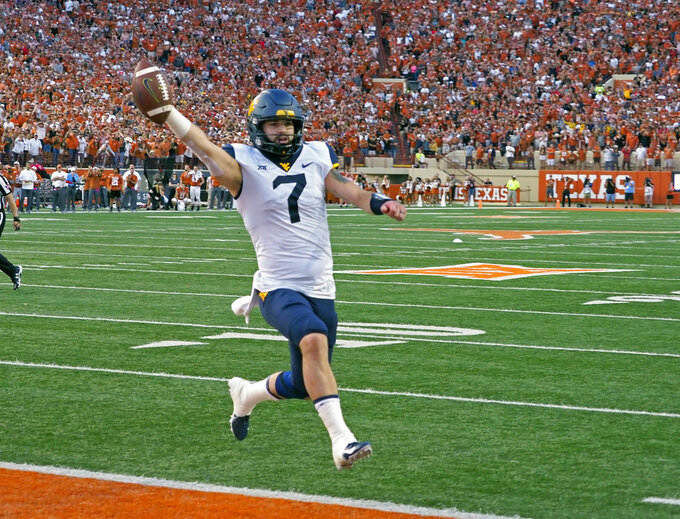 West Virginia quarterback Will Grier runs in the game winning two-point conversion with 16 second to go in an NCAA college football game against Texas, Saturday, Nov. 3, 2018, in Austin, Texas. West Virginia won 42-41. (AP Photo/Michael Thomas)