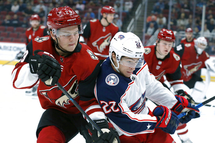 Arizona Coyotes center Barrett Hayton (29) and Columbus Blue Jackets left wing Sonny Milano (22) fight for the puck in the first period during an NHL hockey game, Thursday, Nov. 7, 2019, in Glendale, Ariz. (AP Photo/Rick Scuteri)