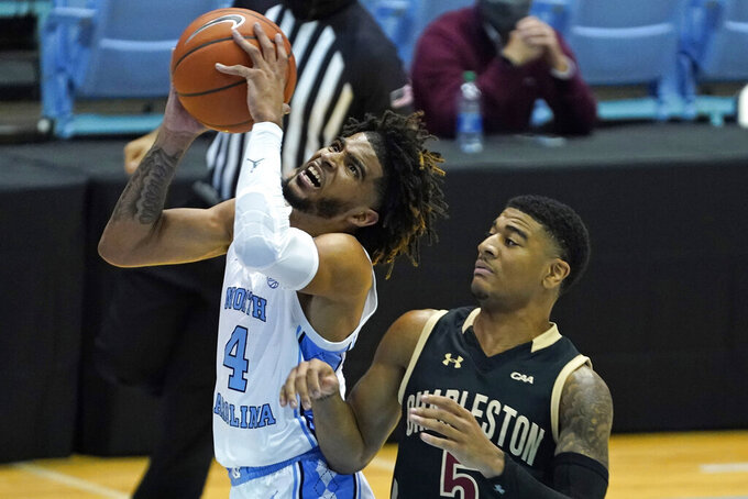 North Carolina guard R.J. Davis (4) grabs the ball next to College of Charleston guard Brenden Tucker (5) during the first half of an NCAA college basketball game in Chapel Hill, N.C., Wednesday, Nov. 25, 2020. (AP Photo/Gerry Broome)