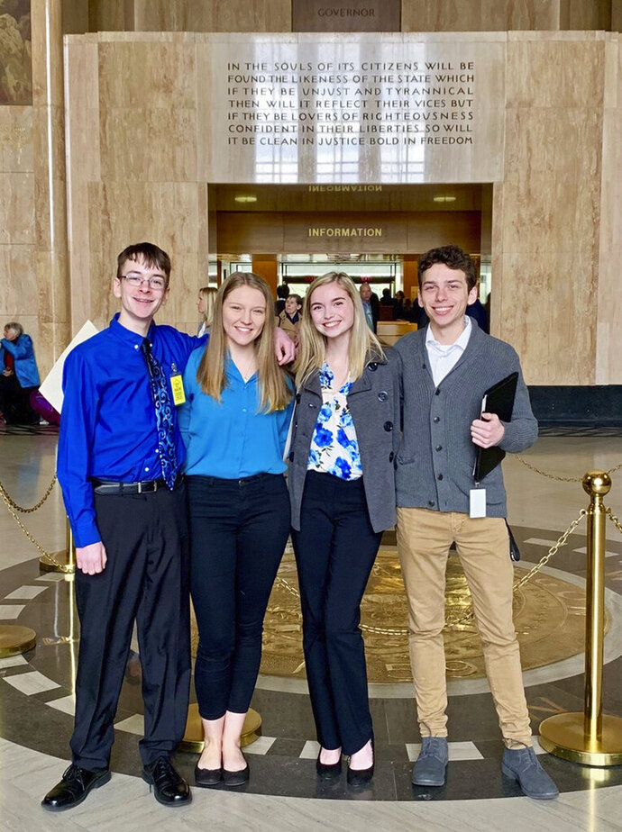 In this Feb. 6, 2019 photo provided by Providence Health & Services, from left, Sam Adamson, Lori Riddle, Hailey Hardcastle, and Derek Evans pose at the Oregon State Capitol in Salem, Ore. The teens introduced legislation to allow students to take