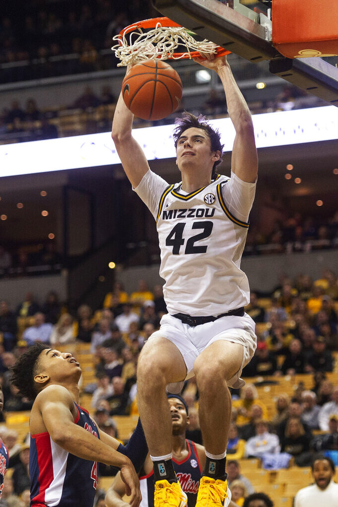 Missouri's Parker Braun, top, dunks the ball over Mississippi's Breein Tyree, left, during the second half of an NCAA college basketball game Tuesday, Feb. 18, 2020, in Columbia, Mo. Missouri won 71-68.(AP Photo/L.G. Patterson)