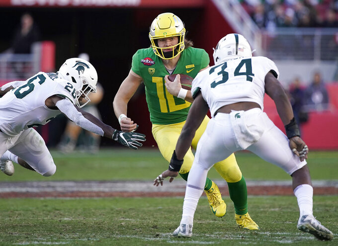 Oregon quarterback Justin Herbert (10) scrabbles out of the pocket between Michigan State linebackers Brandon Bouyer-Randle (26) and Antjuan Simmons (34) during the second half of the Redbox Bowl NCAA college football game Monday, Dec. 31, 2018, in Santa Clara, Calif. Oregon won 7-6. (AP Photo/Tony Avelar)