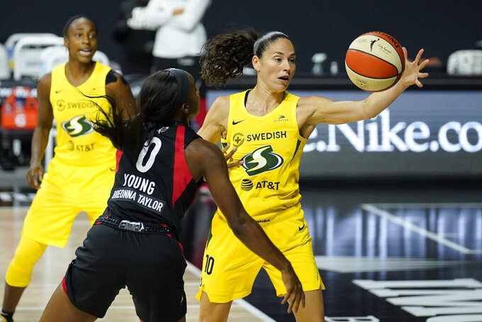 FILE - In this Oct. 6, 2020, file photo, Seattle Storm guard Sue Bird (10) grabs the ball away from Las Vegas Aces guard Jackie Young (0) during Game 3 of basketball's WNBA Finals, in Bradenton, Fla. The Storm winning the league championship, with the biggest margin of victory in WNBA Finals and the fourth title for the franchise, was among Washington state's top stories for 2020. (AP Photo/Chris O'Meara, File)