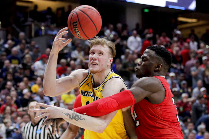 Texas Tech center Norense Odiase, right, fouls Michigan center Jon Teske during the second half an NCAA men's college basketball tournament West Region semifinal Thursday, March 28, 2019, in Anaheim, Calif. (AP Photo/Jae C. Hong)