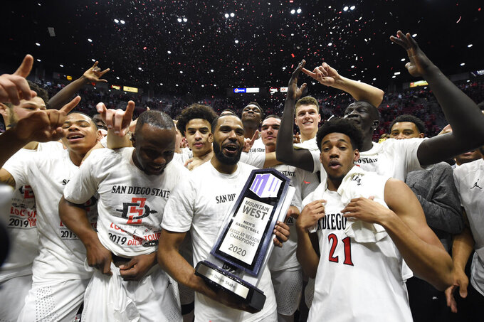 San Diego State guard KJ Feagin (10) holds up the Mountain West Championship trophy after the team defeated New Mexico 82-59 in an NCAA college basketball game, Tuesday, Feb. 11, 2020, in San Diego. (AP Photo/Denis Poroy)