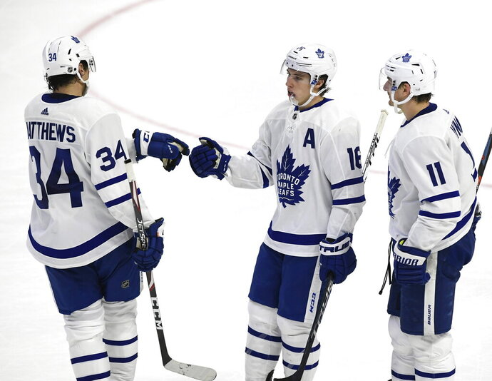 Toronto Maple Leafs right wing Mitchell Marner (16) celebrates his empty-net goal against the Ottawa Senators with center Auston Matthews (34) and left wing Zach Hyman (11) during third-period NHL hockey game action in Ottawa, Ontario, Saturday, Feb. 15, 2020. (Justin Tang/The Canadian Press via AP)