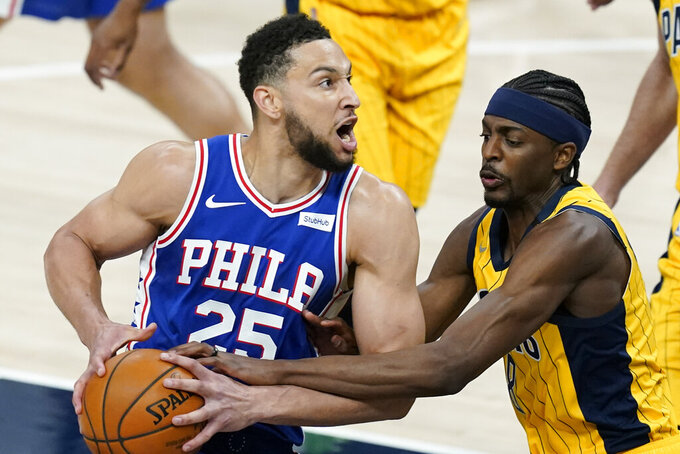 Philadelphia 76ers' Ben Simmons (25) is fouled by Indiana Pacers' Justin Holiday (8) during the first half of an NBA basketball game, Tuesday, May 11, 2021, in Indianapolis. (AP Photo/Darron Cummings)