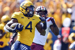 West Virginia running back Leddie Brown (4) rushes for a touchdown against Virginia Tech during the first half of an NCAA college football game in Morgantown, W.Va., Saturday, Sept. 18, 2021. (AP Photo/William Wotring)