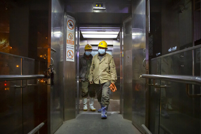 Construction workers wearing face masks to protect against the spread of the coronavirus exit an elevator in Beijing, Wednesday, Jan. 13, 2021. China is concentrating its pandemic prevention efforts in the rural areas as officials urge people to not travel home for the annual Lunar New Year festival, as the country combats its most serious latest outbreak of COVID-19 since the pandemic originally broke out in Wuhan a year ago. (AP Photo/Mark Schiefelbein)