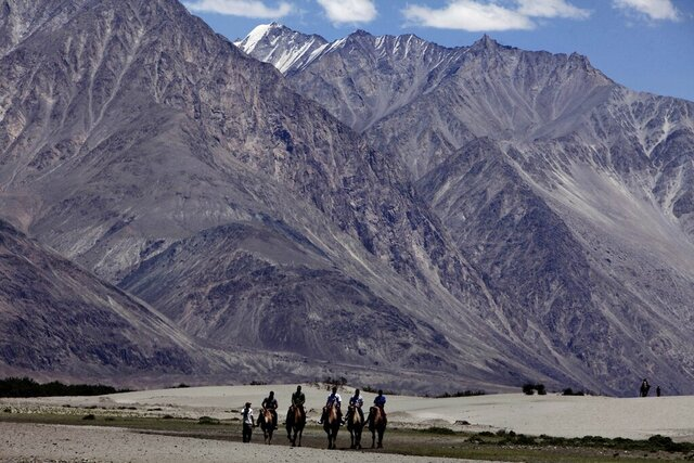 FILE- In this July 20, 2011 file photo, tourists ride double hump camels at Nubra valley, in Ladakh, India. Tensions along the disputed India-China border seem to be getting worse rather than better, three months after their deadliest confrontation in decades in June. The Asian giants accused each other this week of sending soldiers into each other's territory and fired warning shots for the first time in 45 years, raising the specter of full-scale military conflict. (AP Photo/Channi Anand, File)