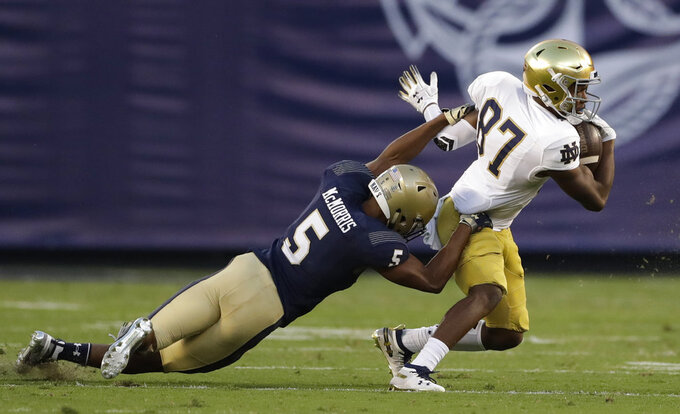 Notre Dame wide receiver Michael Young, right, gets away from Navy defensive back Michael McMorris during the first half of an NCAA college football game Saturday, Oct. 27, 2018, in San Diego. (AP Photo/Gregory Bull)