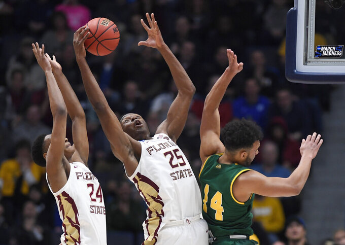 Florida State's Mfiondu Kabengele (25) pulls down a rebound against Vermont's Isaiah Moll (14) as Florida State's Devin Vassell (24) defends during the second half of a first round men's college basketball game in the NCAA tournament, Thursday, March 21, 2019, in Hartford, Conn. (AP Photo/Jessica Hill)